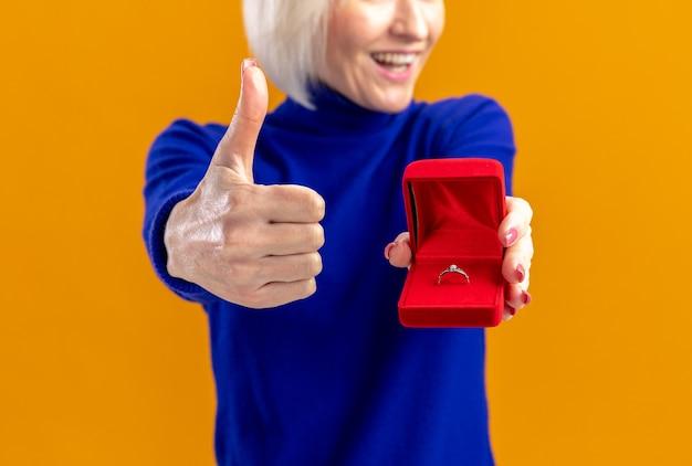 Sorridente bella donna slava che tiene in mano una scatola ad anello rossa e che fa il pollice in alto isolata sulla parete arancione con spazio per le copie