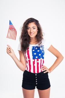 Sorridente ragazza abbastanza teenager che tiene la bandiera usa
