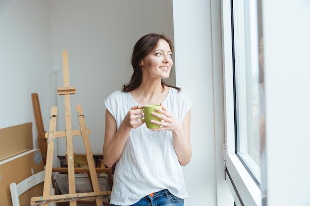 Sorridente artista donna graziosa che beve caffè vicino alla finestra in officina