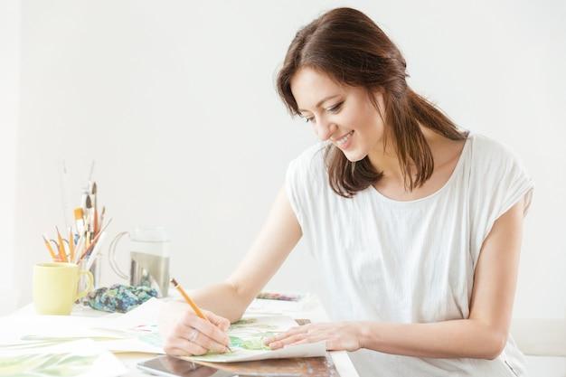 Sorridente bella donna pittore che disegna al tavolo