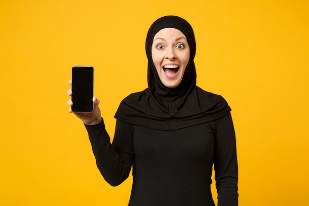 La donna musulmana araba abbastanza giovane sorridente in vestiti neri di hijab tiene in mano il telefono cellulare isolato sul ritratto giallo della parete. concetto di stile di vita religioso della gente. .