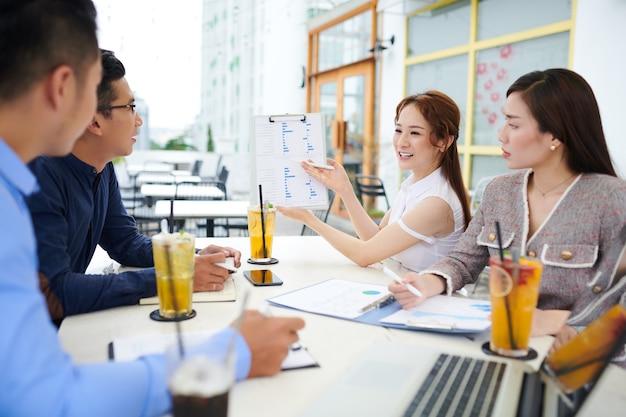 Sorridente piuttosto giovane imprenditrice asiatica che mostra un insieme di grafici quando condivide le sue idee di business con i colleghi alla riunione