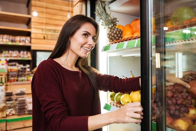 Sorridente bella giovane donna che sceglie e compra frutta al negozio di alimentari