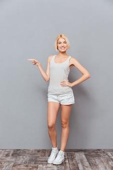 Sorridente bella giovane donna in piedi e che indica via