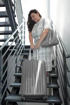 Sorridente bella giovane donna che si sforza di portare una valigia pesante su per le scale o su un condominio senza ascensore