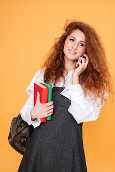 Sorridente bella giovane donna con libri e zaino parlando al cellulare