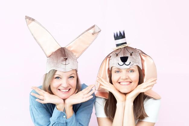 Sorridenti belle giovani donne che indossano orecchie da coniglio su sfondo rosa chiaro