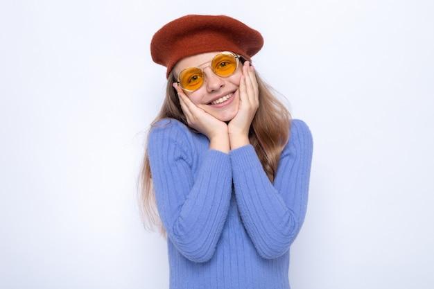 Sorridente mettendo le mani sulle guance bella bambina con gli occhiali con cappello