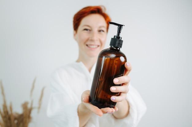 Chimico femminile dai capelli rossi sorridente che presenta una bottiglia di shampoo con una pompa. tenendolo davanti alla telecamera, metti a fuoco l'oggetto.