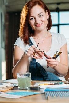 Ritratto sorridente dell'artista della testarossa. hobby di pittura. studio sul posto di lavoro con schizzi intorno.