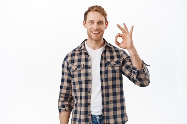 Uomo sorridente dai capelli rossi con una faccia onesta e sincera, garantisce la qualità, mostra il segno ok ok come tutto sotto controllo, assicura e consiglia, dà un feedback positivo, loda il prodotto