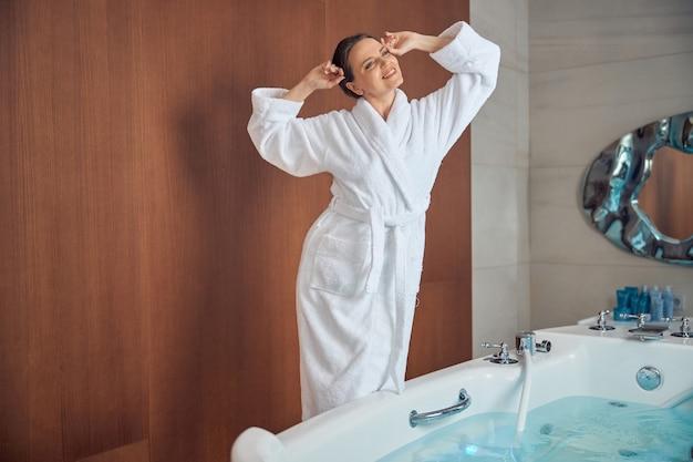 Sorridente rilassata giovane donna caucasica dai capelli scuri con le braccia alzate che si allunga prima della vasca da bagno