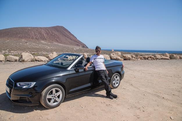 L'uomo ricco sorridente posa con la sua auto decappottabile, è estate, è in vacanza sulla spiaggia e si gode la vita.