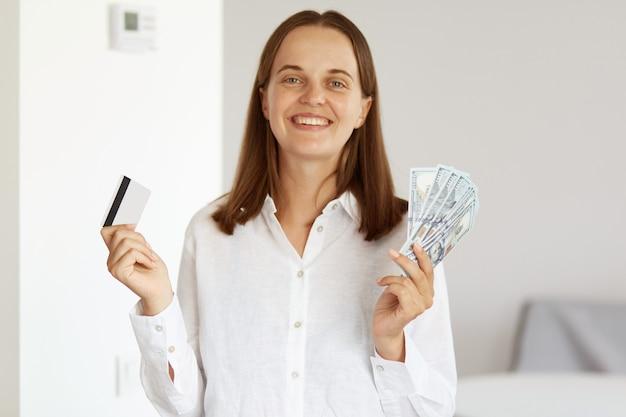 Sorridente donna ricca che indossa una camicia bianca in stile casual, vincendo alla lotteria, tenendo in mano carta di credito e banconote in dollari, guardando la telecamera con espressione felice, in posa in una stanza luminosa a casa.