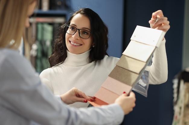 L'assistente di vendita sorridente mostra i campioni con la selezione dei tessuti del tessuto per l'interno domestico