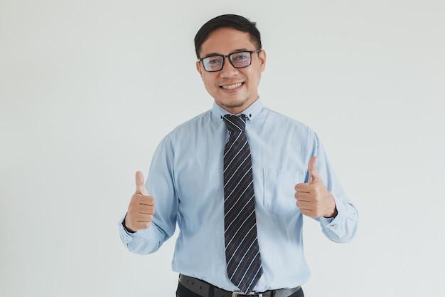 Sorridente addetto alle vendite che indossa camicia blu cravatta e occhiali in posa con il pollice in alto su sfondo bianco