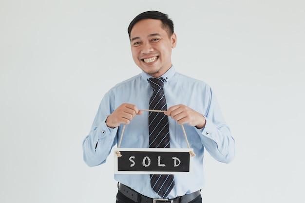 Sorridente addetto alle vendite che indossa camicia blu e cravatta in posa con il cartello venduto di trasporto alla telecamera su sfondo bianco
