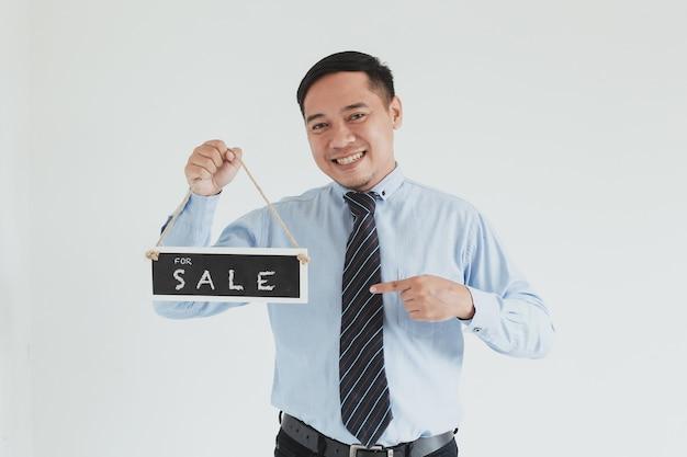 Sorridente uomo di vendita che indossa camicia blu e cravatta in posa con puntamento e portando cartello vendita su sfondo bianco