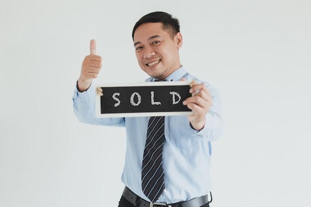Sorridente addetto alle vendite che indossa camicia blu e cravatta in posa con il pollice in alto e mostra il cartello venduto alla telecamera su sfondo bianco