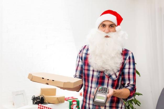 Babbo natale sorridente tiene in mano una scatola di pizza e un terminale pos. babbo natale consegna la pizza per natale, guarda nella telecamera con un sorriso