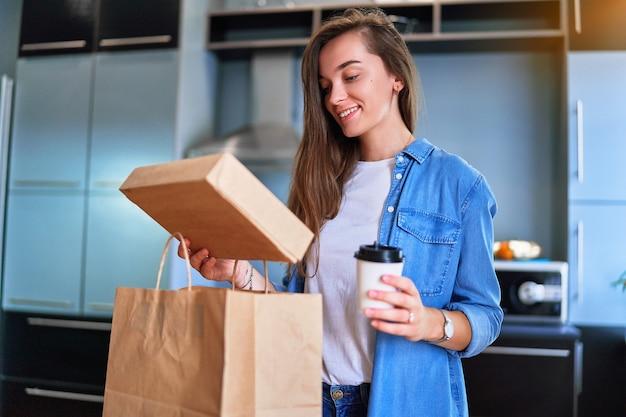 Sorridente soddisfatto felice casual adulto gioioso giovane ragazza millenaria cliente ha ricevuto sacchetti di cartone con cibo e bevande da asporto a casa. concetto di servizio di consegna veloce