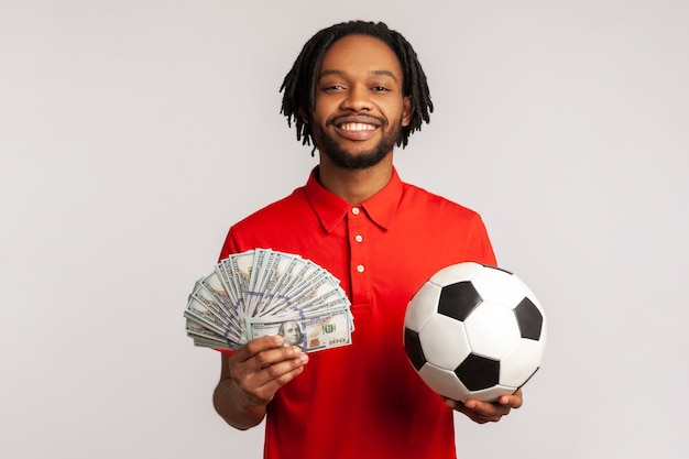 Sorridente uomo soddisfatto con pallone da calcio e fan di banconote da un dollaro, scommesse sportive, grande vittoria.