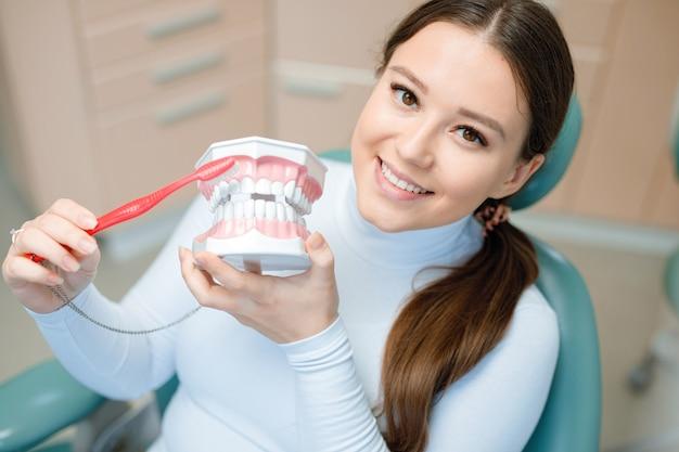 Paziente sorridente e soddisfatto presso l'ufficio del dentista dopo il trattamento.