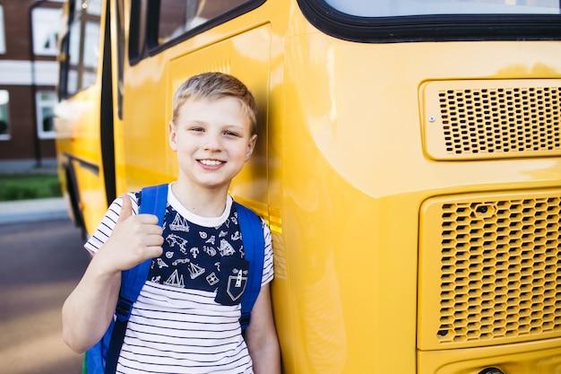 Lo scolaro sorridente della scuola elementare mostra un pollice in alto davanti allo scuolabus. di nuovo a scuola. formazione scolastica. giorno della conoscenza.