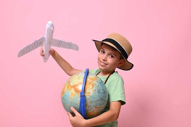 Scolaro sorridente, turista, che guarda la telecamera mentre gioca con un aeroplano di carta e un globo