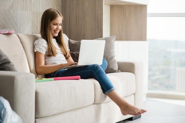 La ragazza sorridente della scuola si siede con il computer portatile al divano bianco