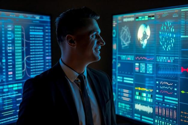 Lo scienziato sorridente che lavora con grandi monitor blu nel laboratorio oscuro