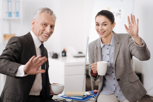 Sorridente segretario e manager seduto sul tavolo tenendo le tazze in mano mentre guarda dritto davanti