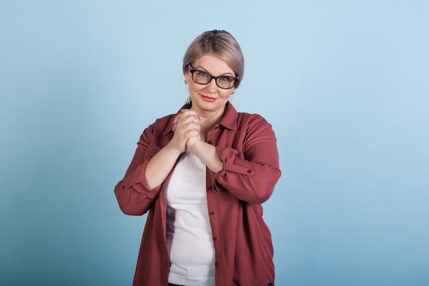 La donna caucasica senior sorridente sta gesticolando il segno di sorpresa mentre guarda l'obbiettivo su una parete blu dello studio