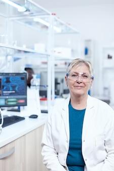 Chimico senior sorridente che indossa occhiali protettivi con provette dietro. scienziato anziano che indossa camice da laboratorio che lavora per sviluppare un nuovo vaccino medico con un assistente africano sullo sfondo.