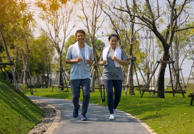 Sorridente coppia senior fare jogging, coppia senior fare jogging e correre nella natura all'aperto del parco