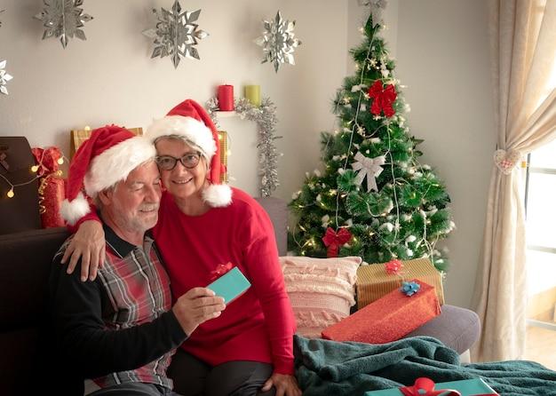 Sorridente coppia senior di due nonni con cappelli di babbo natale che si abbracciano con albero di natale e regali per la famiglia sullo sfondo. amore e concetto di famiglia