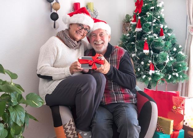 Una coppia anziana sorridente che indossa un cappello da babbo natale dopo aver preparato i regali e le decorazioni natalizie riposa con in mano un tablet legato con l'arco - buon natale a casa per il pensionato anziano in attesa della famiglia