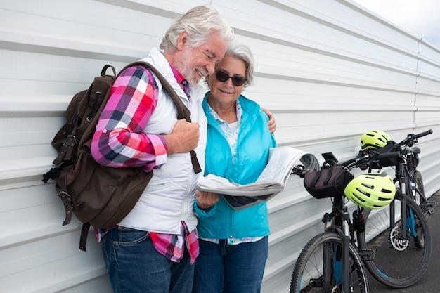Sorridente coppia senior con i capelli grigi in piedi contro un muro di metallo bianco vicino alle loro biciclette elettriche. leggendo le ultime notizie sul giornale.