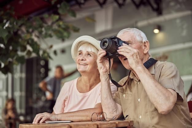 Sorridente signora anziana con un cappello da sole seduta con un fotografo maschio in una caffetteria