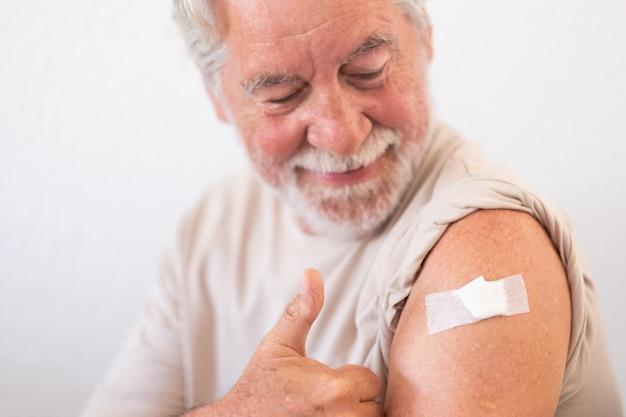Sorridente uomo anziano degli anni '70 dopo aver ricevuto il vaccino contro il coronavirus covid-19.