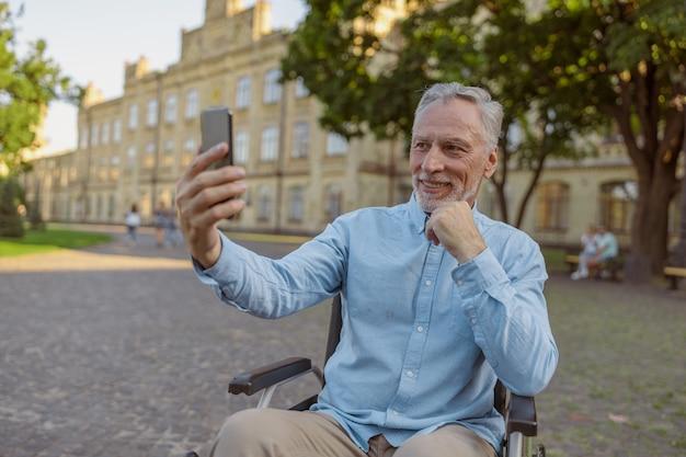 Sorridente uomo anziano che recupera un paziente in sedia a rotelle che fa una videochiamata utilizzando lo smartphone mentre