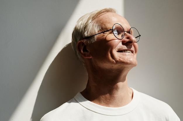 Sorridente uomo anziano alla luce del sole