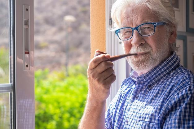 Sorridente uomo anziano alla finestra che guarda la telecamera mentre fuma la pipa