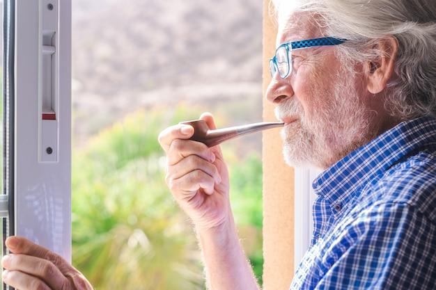 Sorridente uomo anziano alla finestra che guarda fuori mentre fuma la pipa