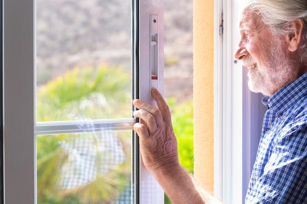 Uomo anziano sorridente alla finestra che guarda fuori