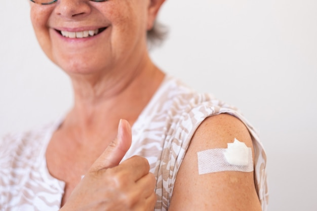 Sorridente donna anziana degli anni '70 dopo aver ricevuto il vaccino contro il coronavirus covid-19.