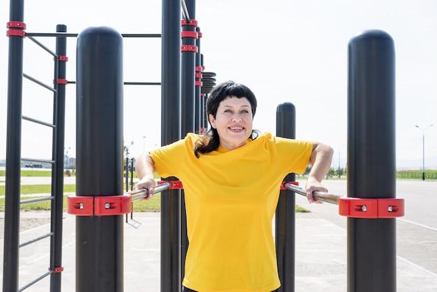 Sorridente donna senior facendo push up inverso all'aperto sulle barre del campo sportivo
