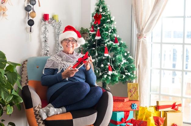 Sorridente donna anziana che indossa un cappello di babbo natale dopo aver preparato regali e decorazioni natalizie riposa in possesso di un tablet legato con l'arco - buon natale a casa per pensionato anziano in attesa della famiglia