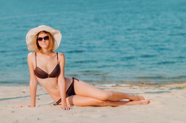 Sorridente giovane donna snella caucasica sexy in occhiali e cappello sulla spiaggia, seduto sulla sabbia dorata. ricreazione e coccole in riva al mare (oceano, fiume, lago) in estate e nelle giornate di sole.