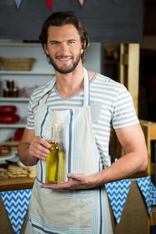 Assistente di negozio sorridente che tiene la bottiglia di olio d'oliva